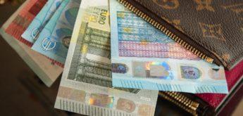 In einem Schraubwerkzeug geklemmte Münzen neben Bilanzübersicht und Taschenrechner.