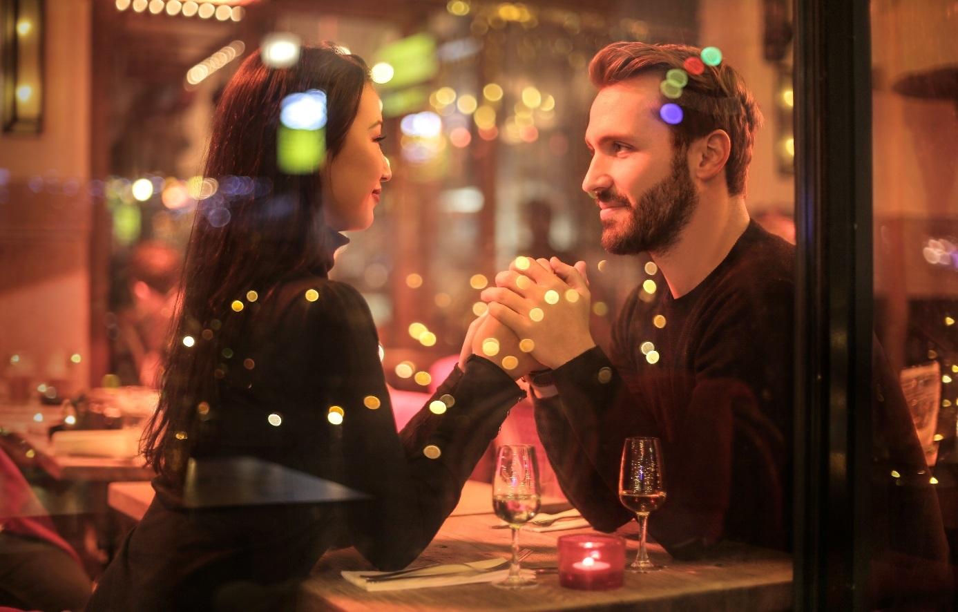 Paar sitzt Hand in Hand am Tisch