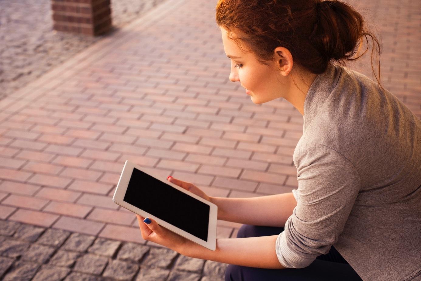 Junge Frau sitzt auf dem Boden und liest auf ihrem Tablet.  [Copyright = Anna Damianenko / unsplash.com]