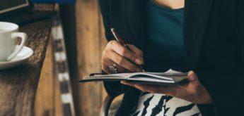 Frau schreibt in ein Notizbuch und trinkt Kaffee.