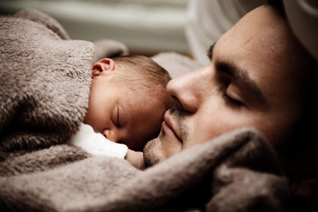 Ein junger Papa schläft mit seinem Baby auf dem Bauch unter einer braunen Kuscheldecke.