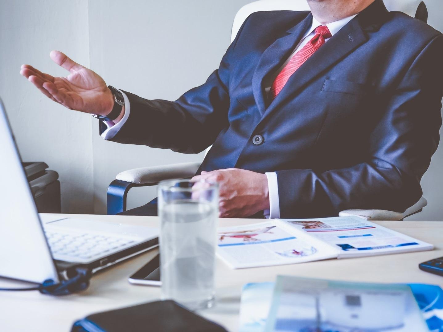 Mann im Anzug sitzt am Schreibtisch