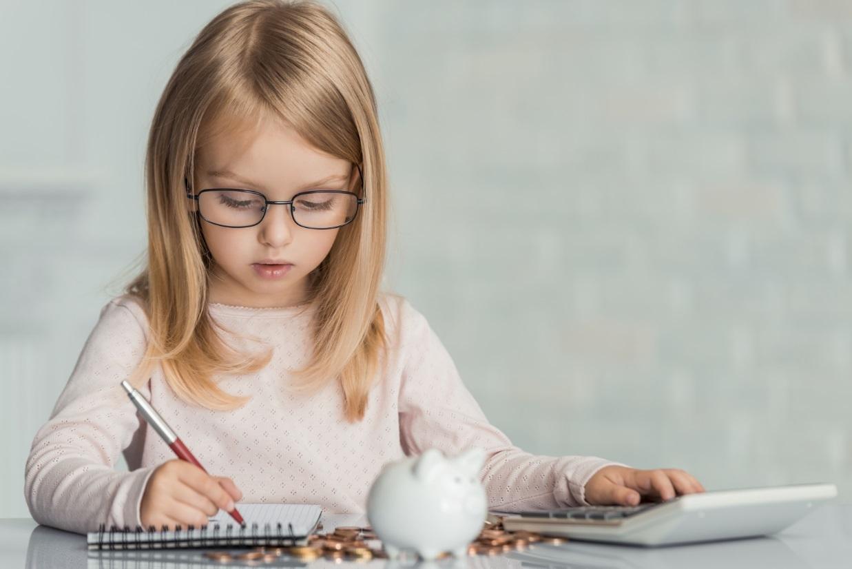 Mädchen sitzt mit Taschenrechner und Sparschwein am Tisch.