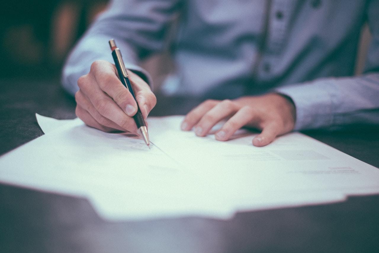 Ein Mann füllt ein Dokumente aus.