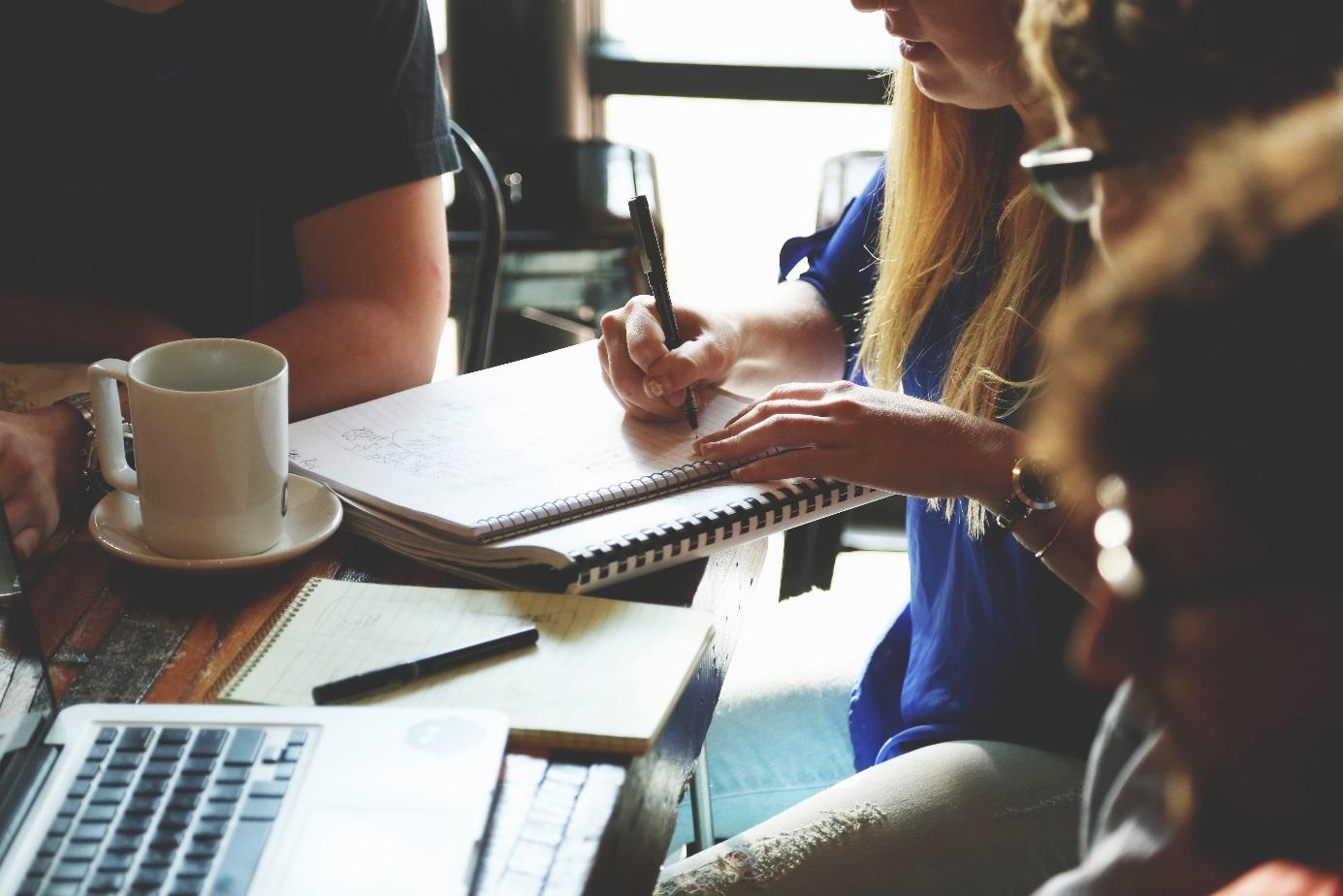 Vier Personen sitzen an einem Tisch mit Arbeitsunterlagen.