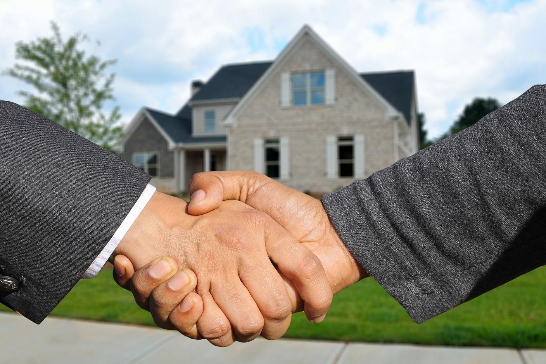 Händeschütteln vor dem Wohnhaus.