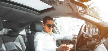 Mann mit Sonnenbrille und Smartphone im Auto-Cockpit.