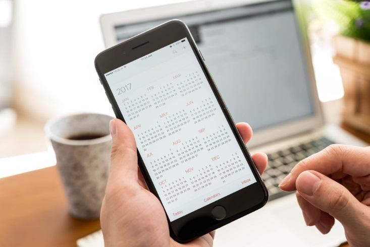 Hand hält Smartphone mit Kalender-App auf dem Display.
