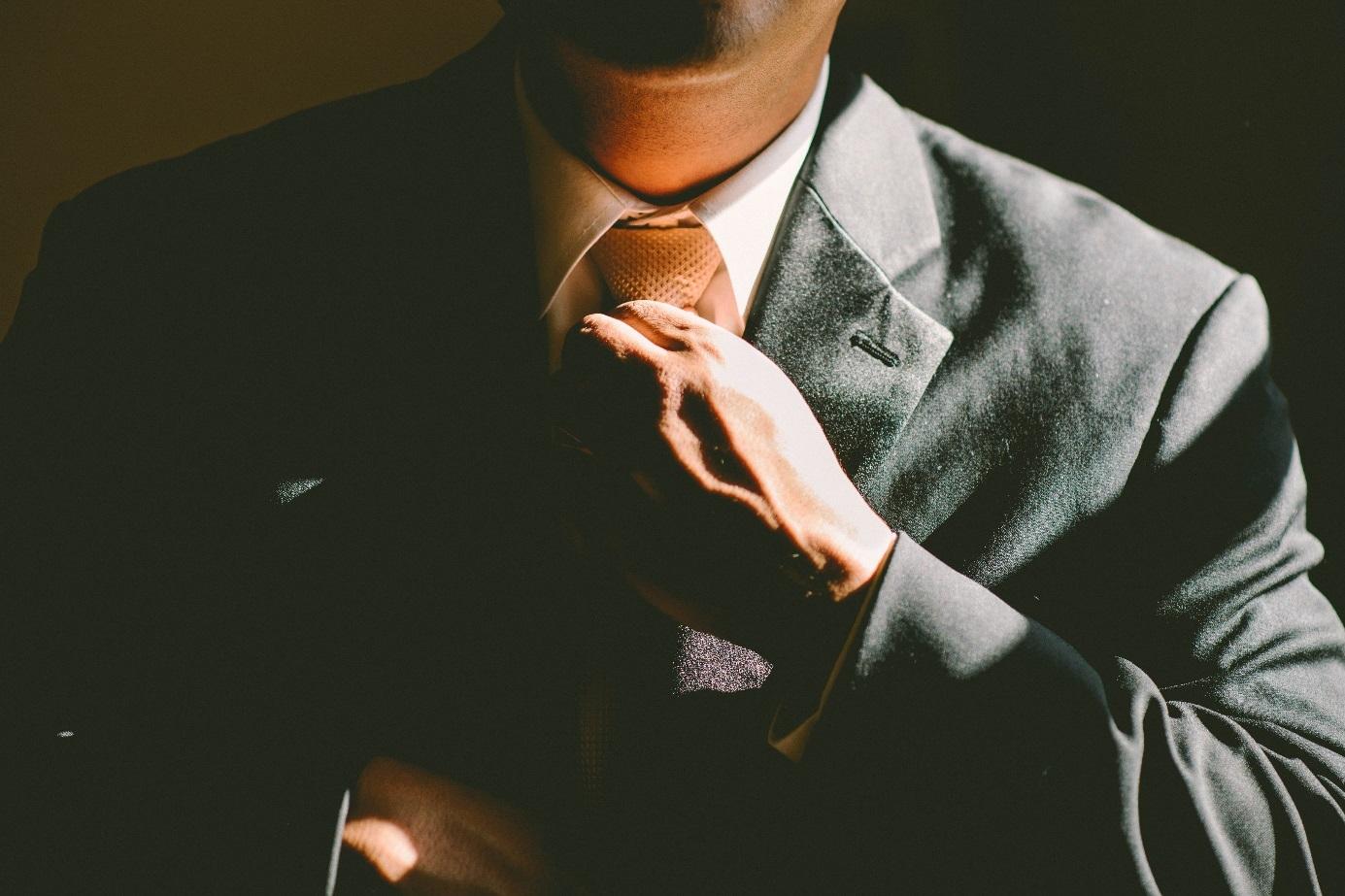 Mann schiebt sich seine Krawatte zurecht.