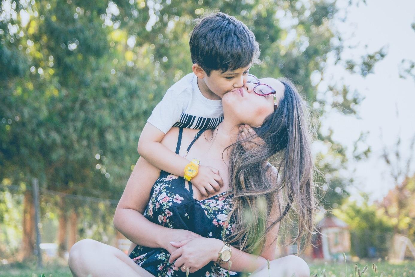 Sohn küsst Mutter und umarmt sie