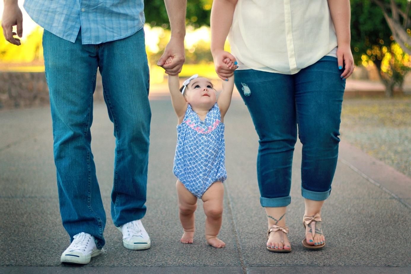 Eltern halten Kleinkind an den Händen