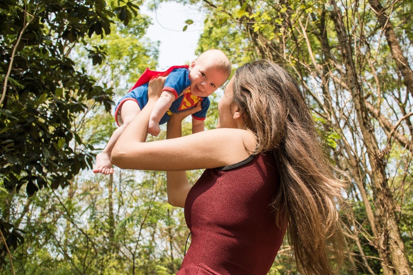 Mutter hält fröhliches Baby hoch