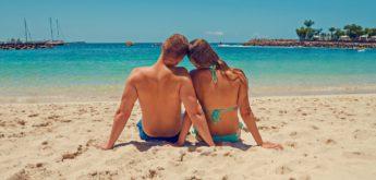 Paar sitzt am Strand.