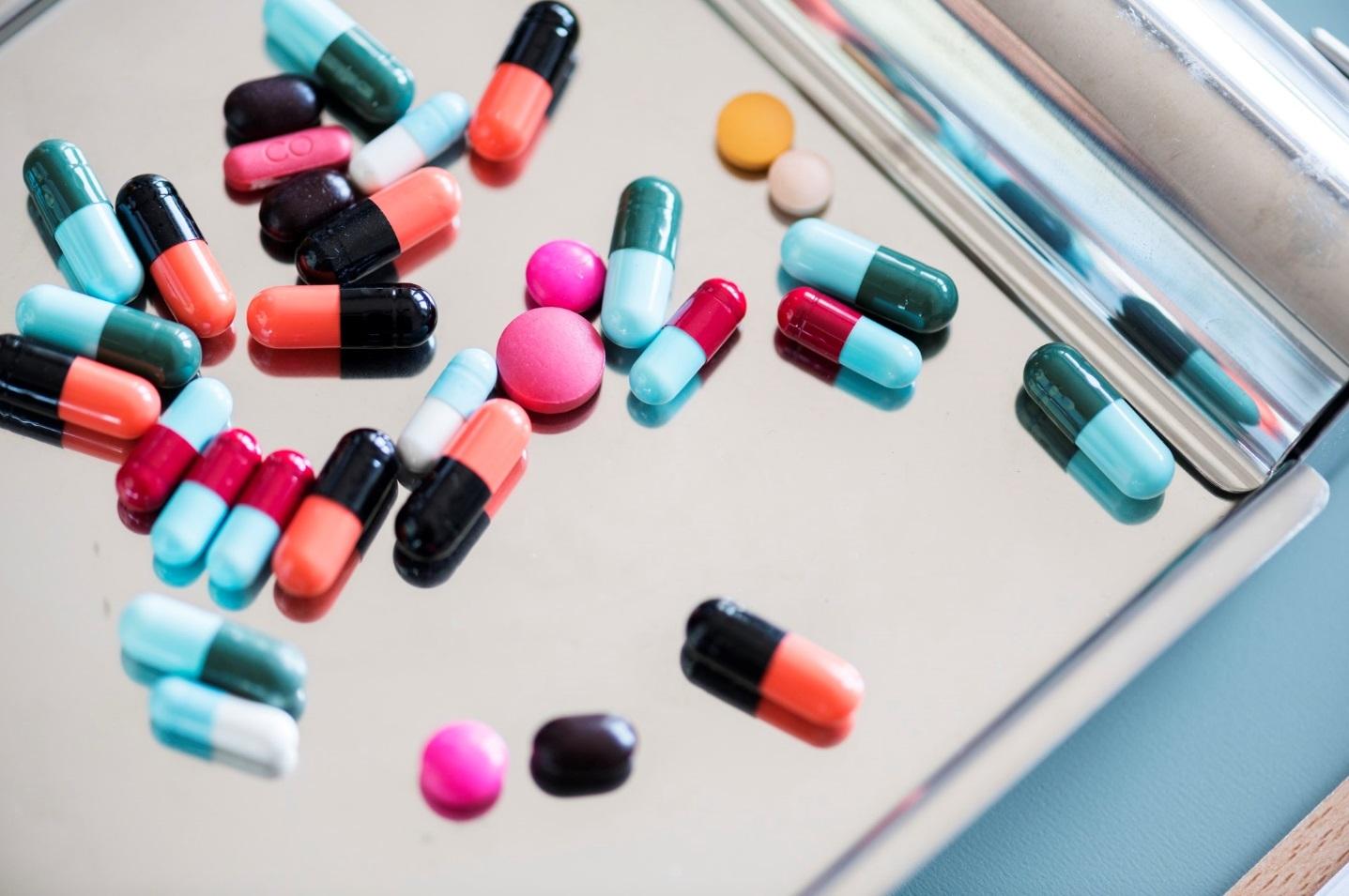 Verschiedene Medikamente liegen auf Metallplatte.