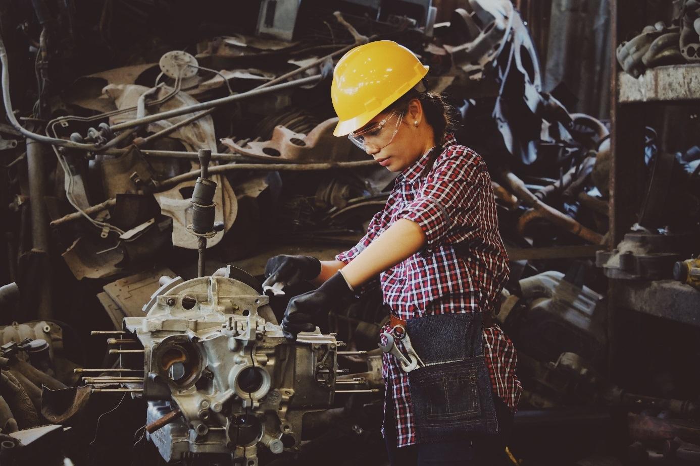 Junge Frau mit Helm bedient eine Industriemaschine.