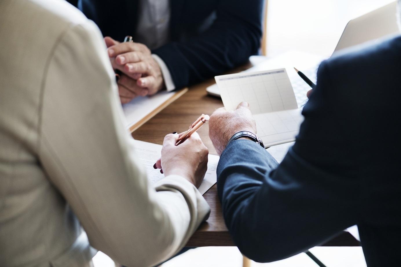 Drei Menschen im Anzug sitzen sich an einem mit Schreibutensilien beladenen Tisch gegenüber.