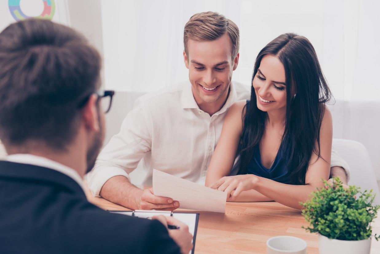 Junges fröhliches Paar liest ein Schriftstück. Ihnen gegenüber sitzt ein Mann im Anzug.