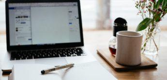 Schreibtisch mit Notebook, Notizbuch und Kaffeetasse.