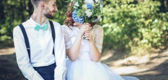 Bräutigam mit Braut, die sich Blumenstrauß vor das Gesicht hält.
