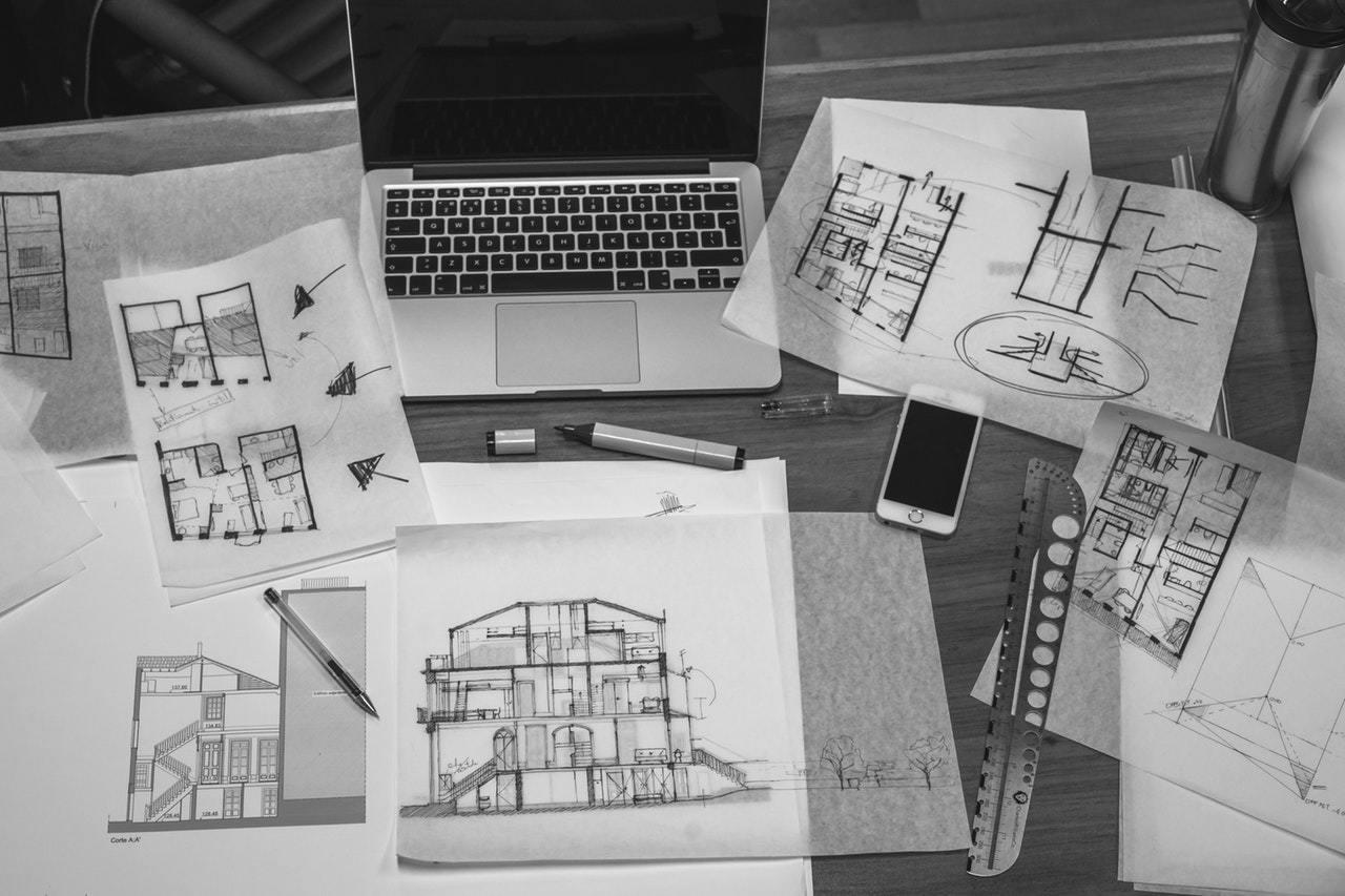 Grundriss-Skizzen und Laptop auf einem Schreibtisch .