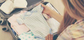Frau packt Babysachen in einen Koffer.