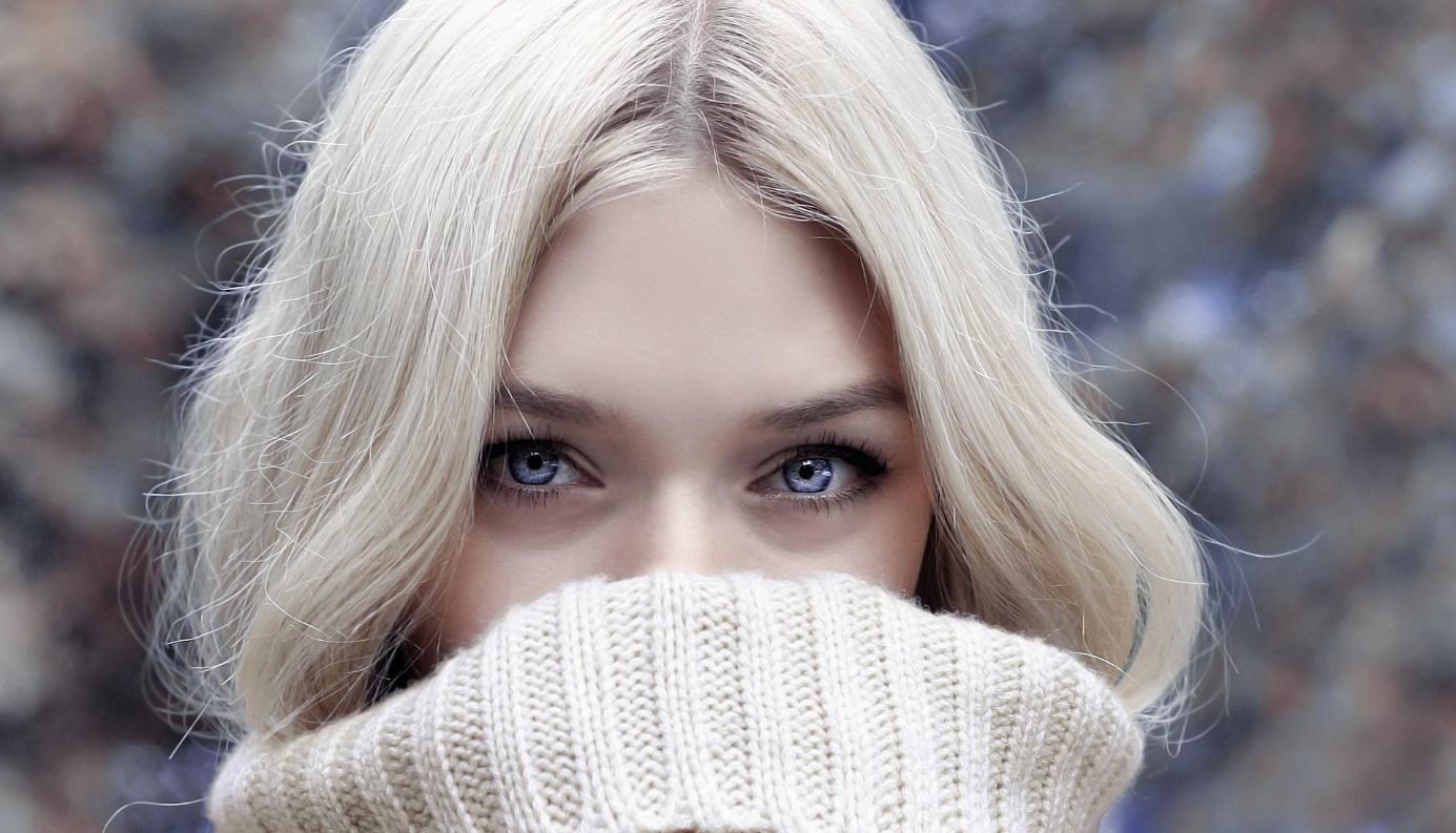 Blonde Frau versteckt Gesicht unter Rollkragenpullover