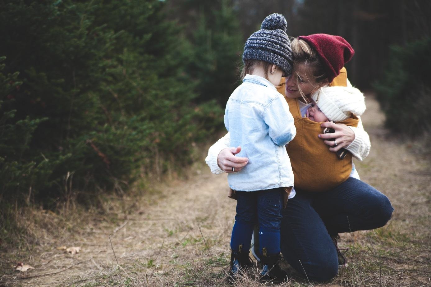 Frau trägt Baby und umarmt Kleinkind.
