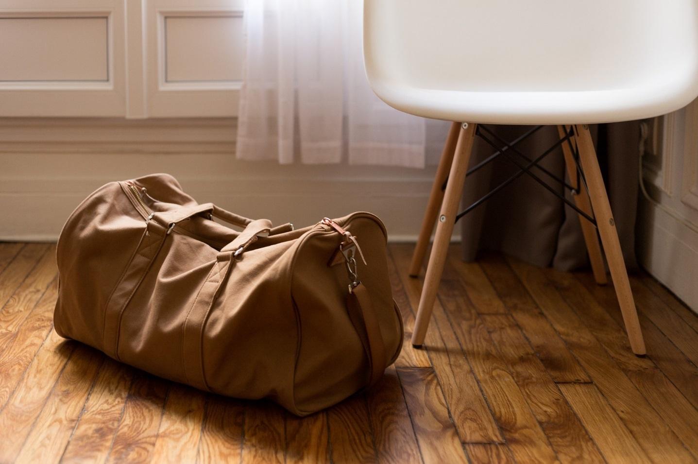 Braune Reisetasche neben Stuhl.