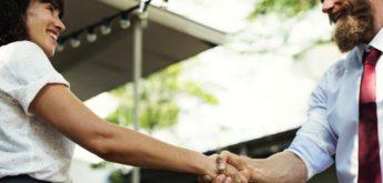 Eine Frau und ein Mann in Businesskleidung geben sich die Hand.
