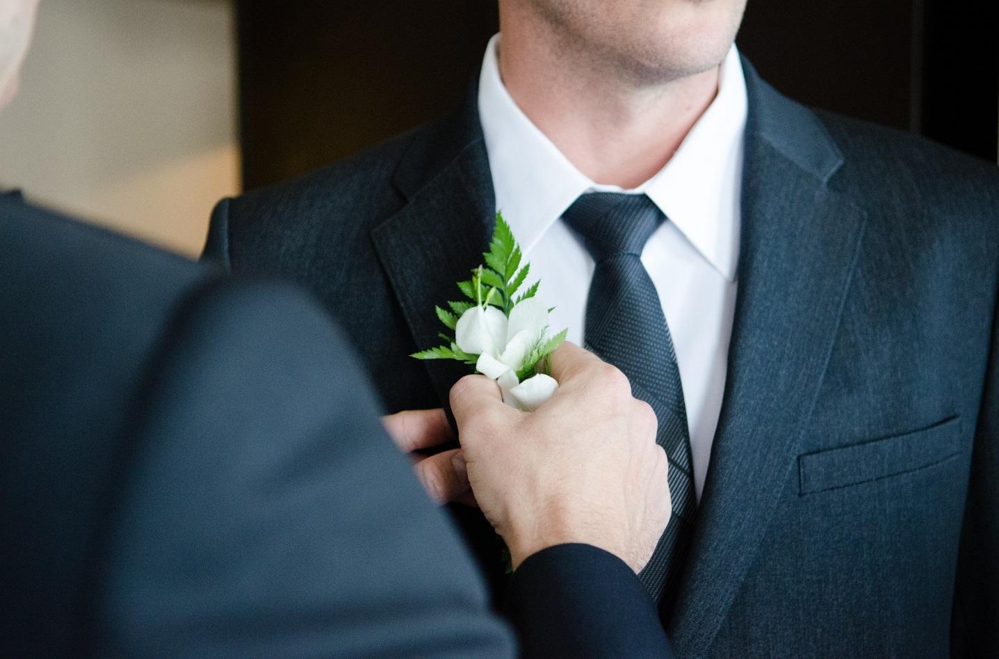 Bräutigam in Anzug bekommt Blume ins Knopfloch.