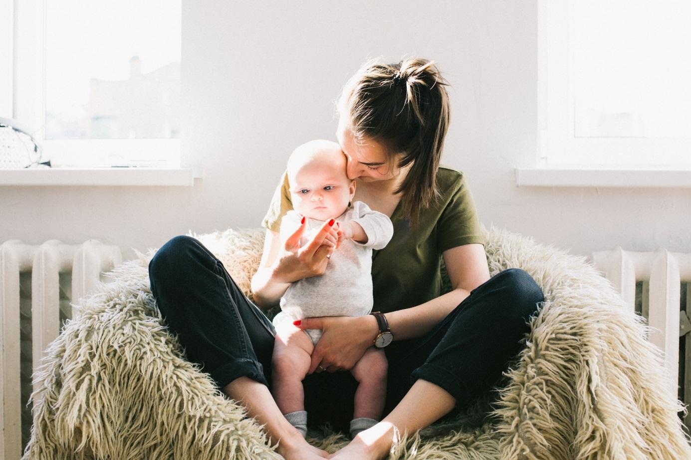 Frau sitzt auf Sessel und hält Baby.