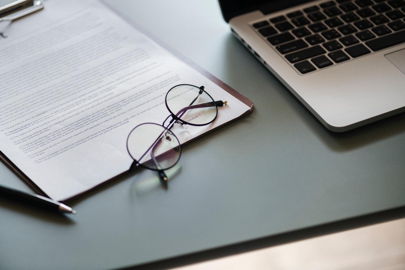 Laptop, Bewerbungsmappe und Brille
