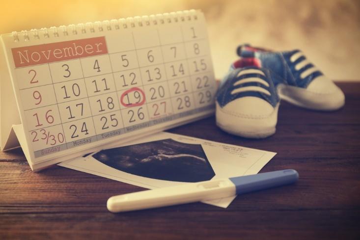 Ein Tisch mit Kalender, Schwangerschaftstest und Babyschuhen.