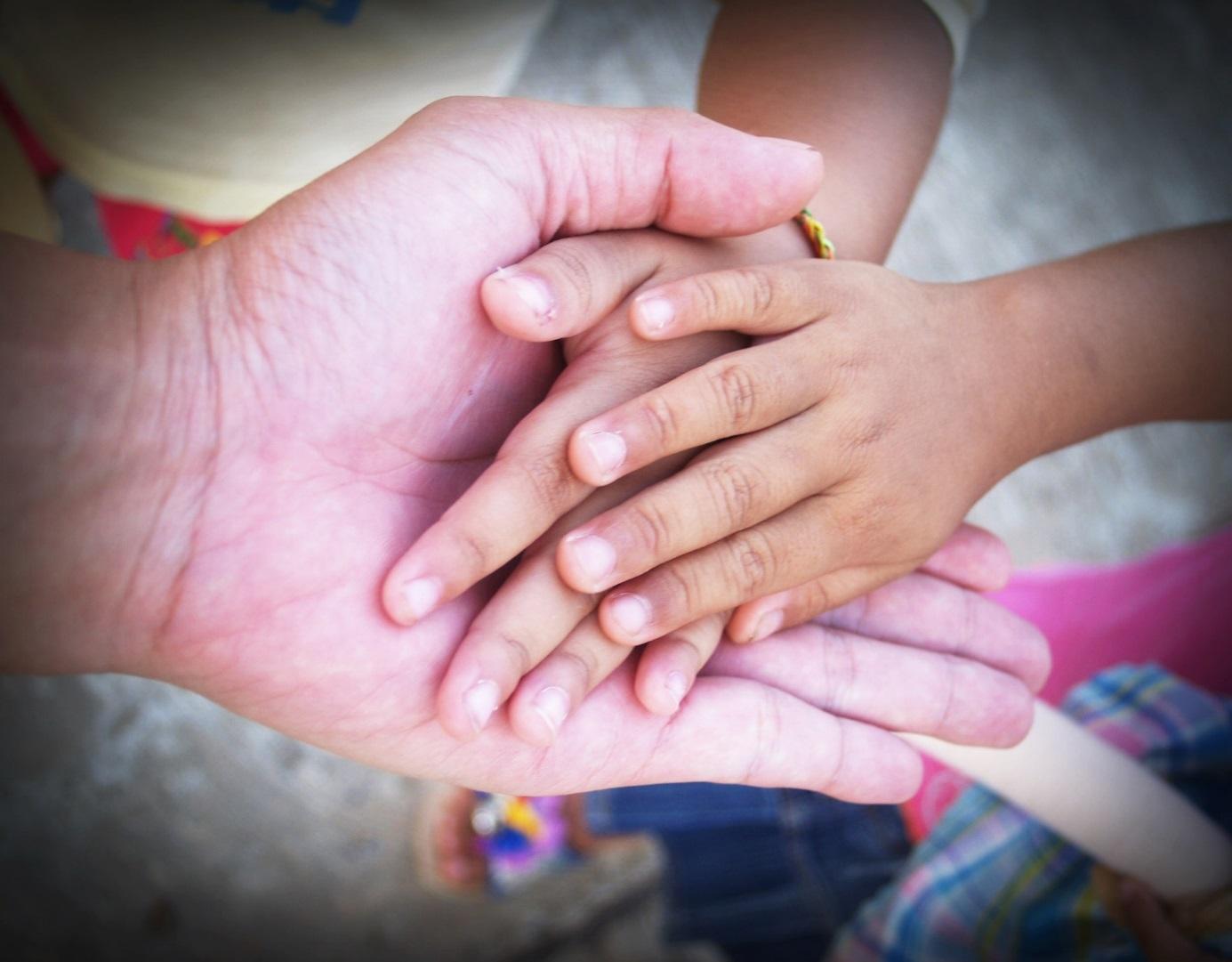 Kinder- und Erwachsenenhände unfassen sich. [Copyright = imagesthai.com / pexels.com]