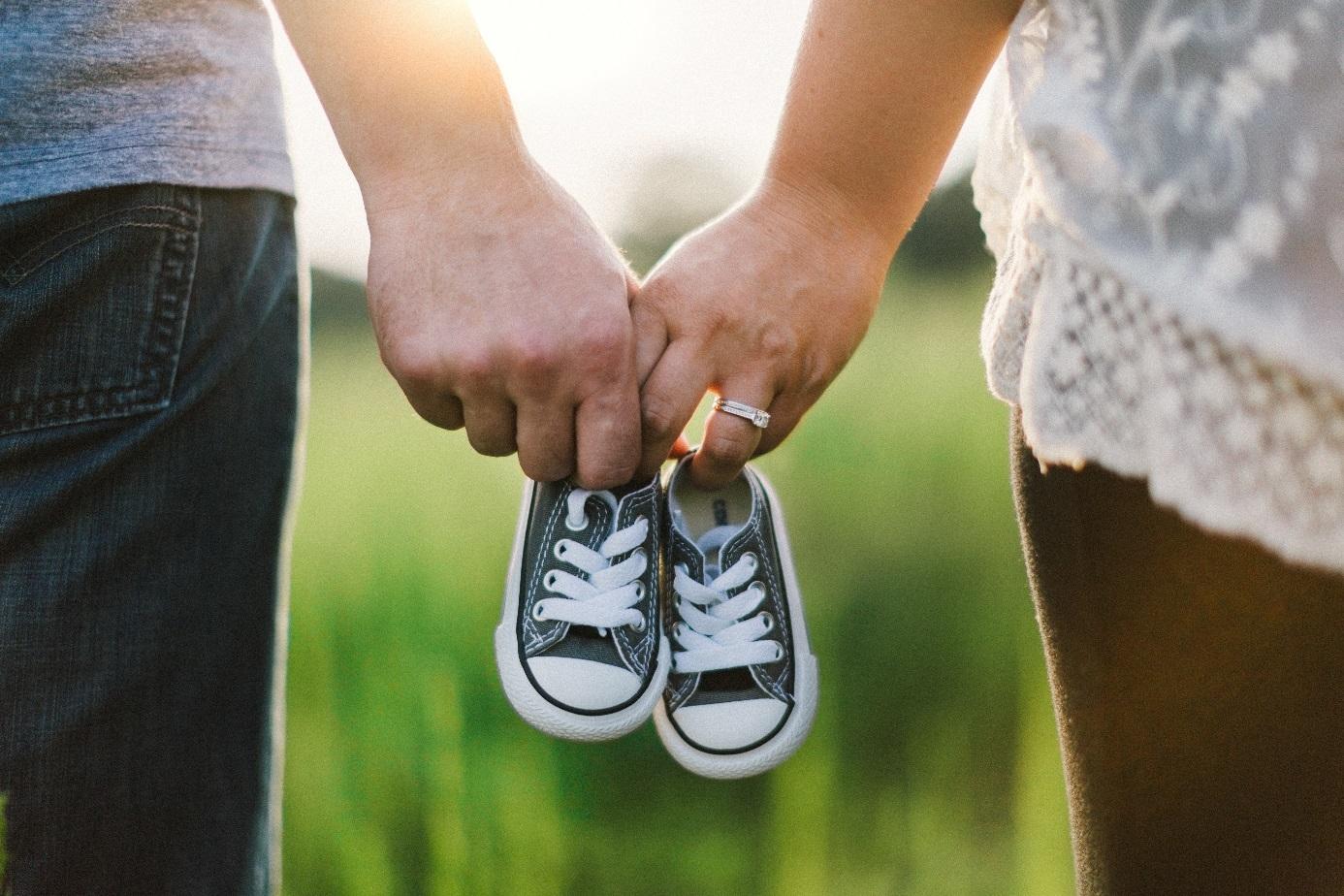 Ein Mann und eine Frau halten zusammen ein Paar Babyschuhe.