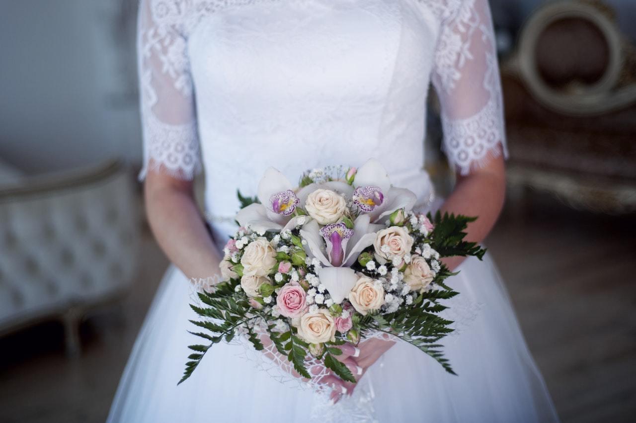 Frau in Hochzeitskleid hält Blumenstrauß