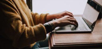 Junge Frau tippt auf einem Laptop.