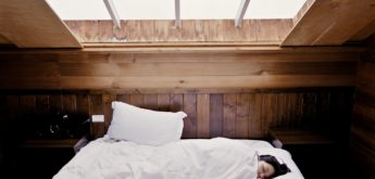 Eine Frau schläft, bis zum Kinn zugedckt, im weißen Bett.
