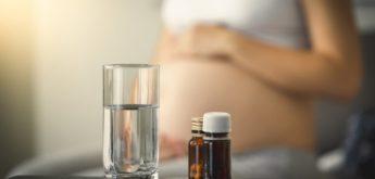 Verschiedene Tabletten und ein Glas Wasser, im Hintergrund eine schwangere Frau.