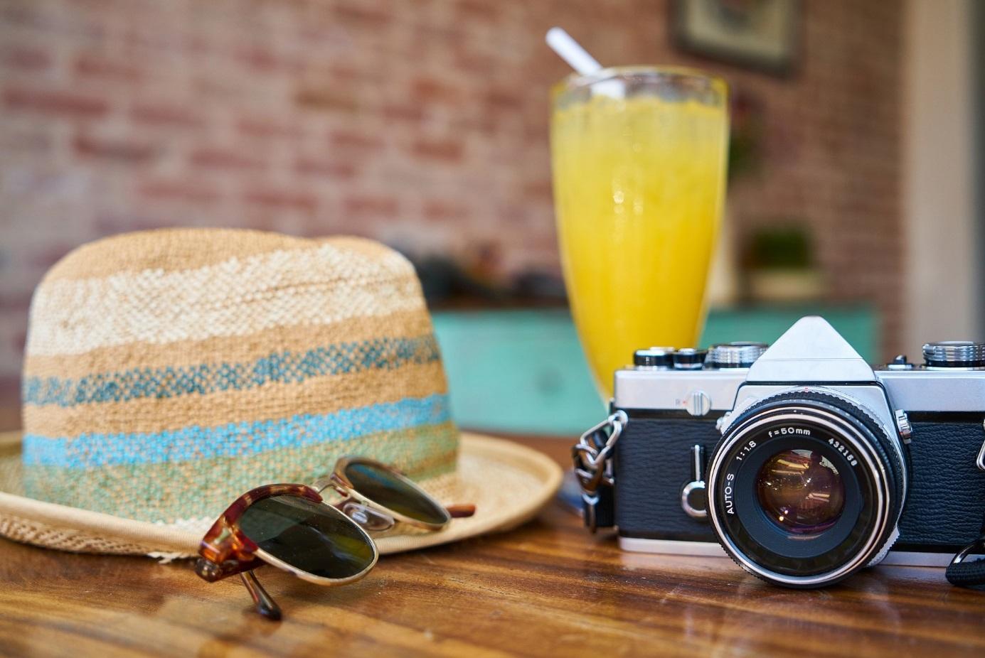 Sonnenhut, Sonnenbrille, Kamera und Drink auf einem Tisch arrangiert.