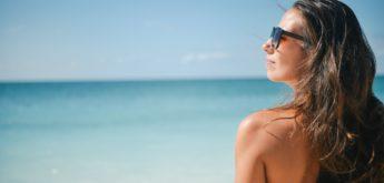 Frau mit Sonnenbrille am Meer unter blauem Himmel.