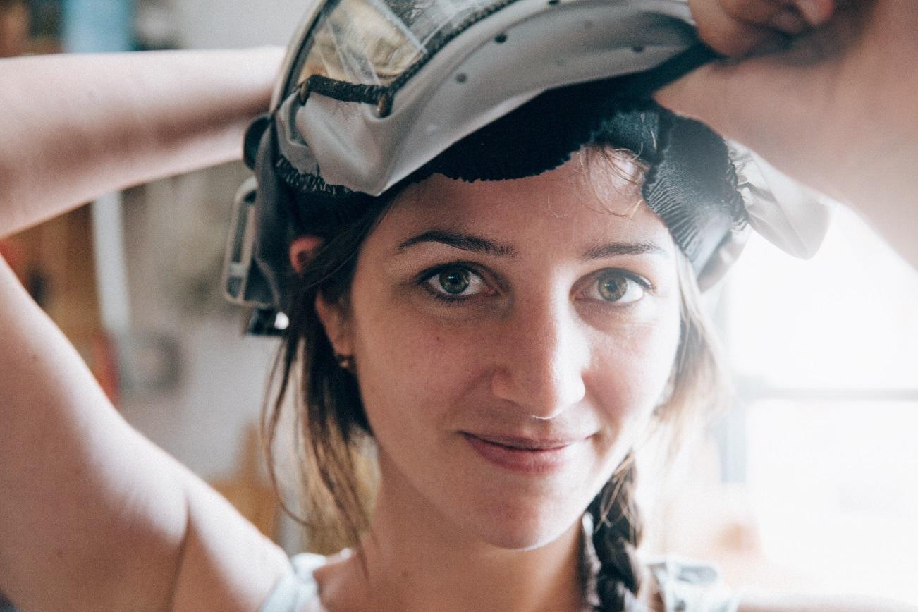 Junge Frau setzt sich einen Helm auf.