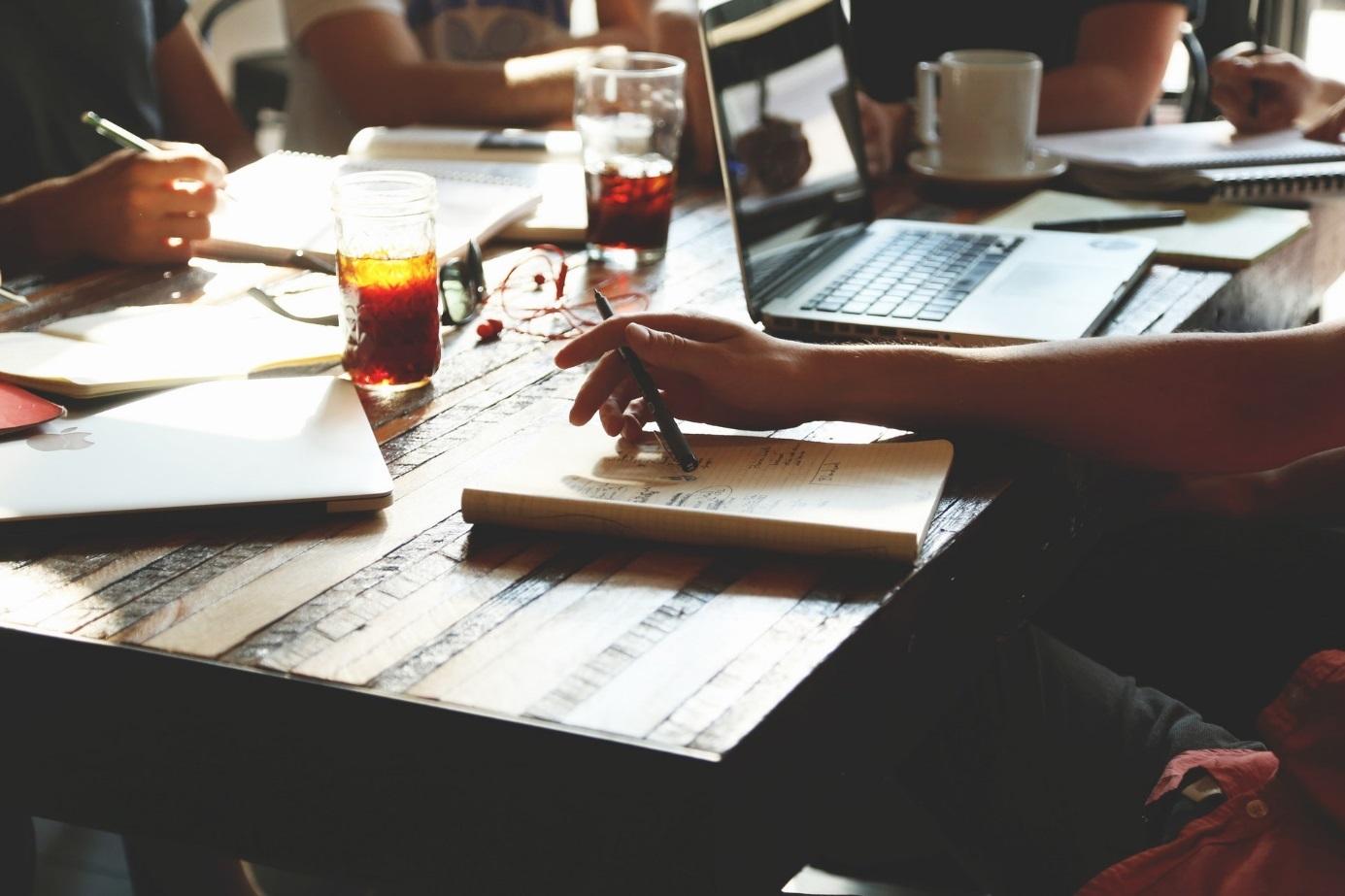 Am Schreibtisch sitzende Menschen mit Stift in Hand, Laptop und Büchern.