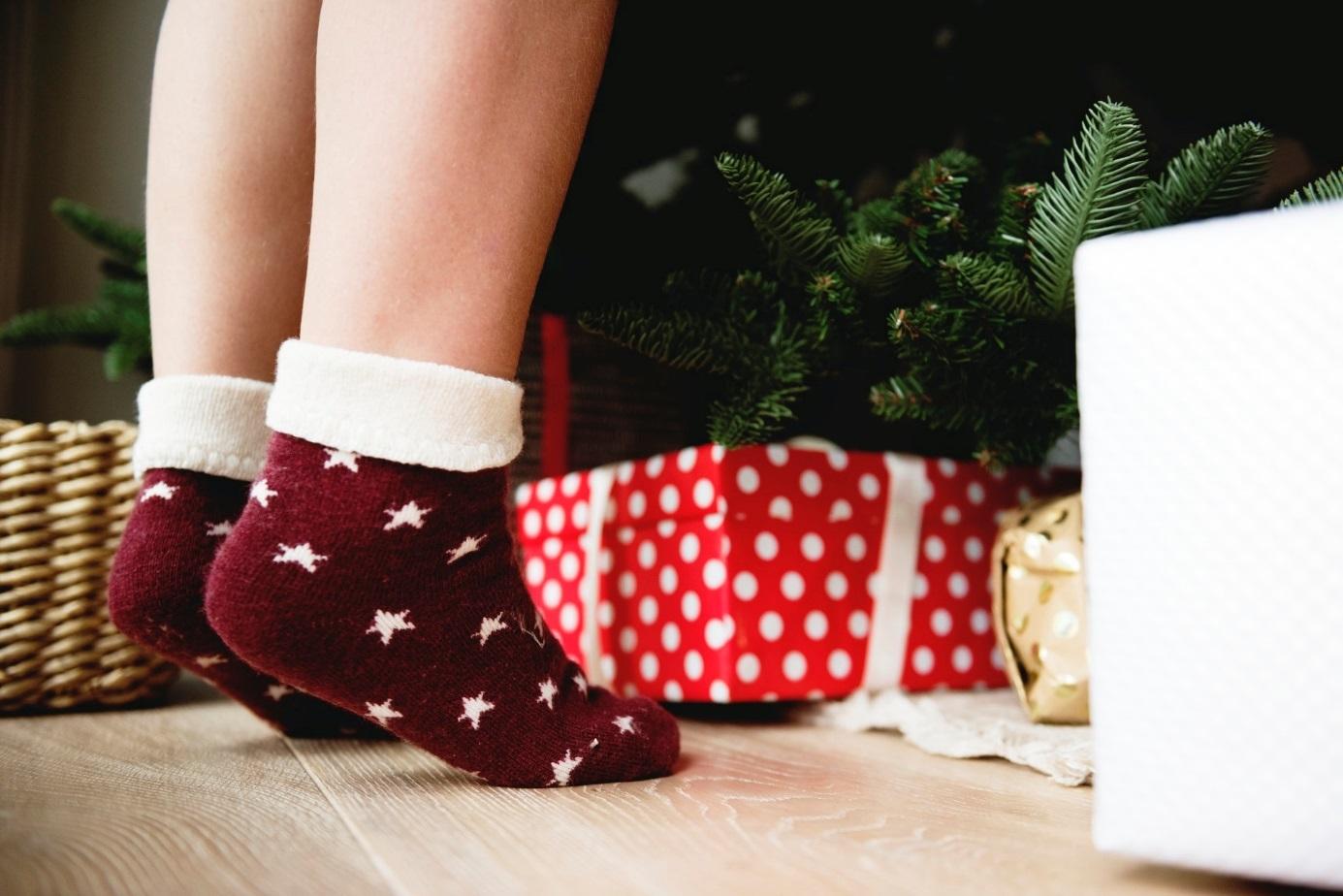 Kind in roten Socken vor Geschenken und Weihnachtsbaum.