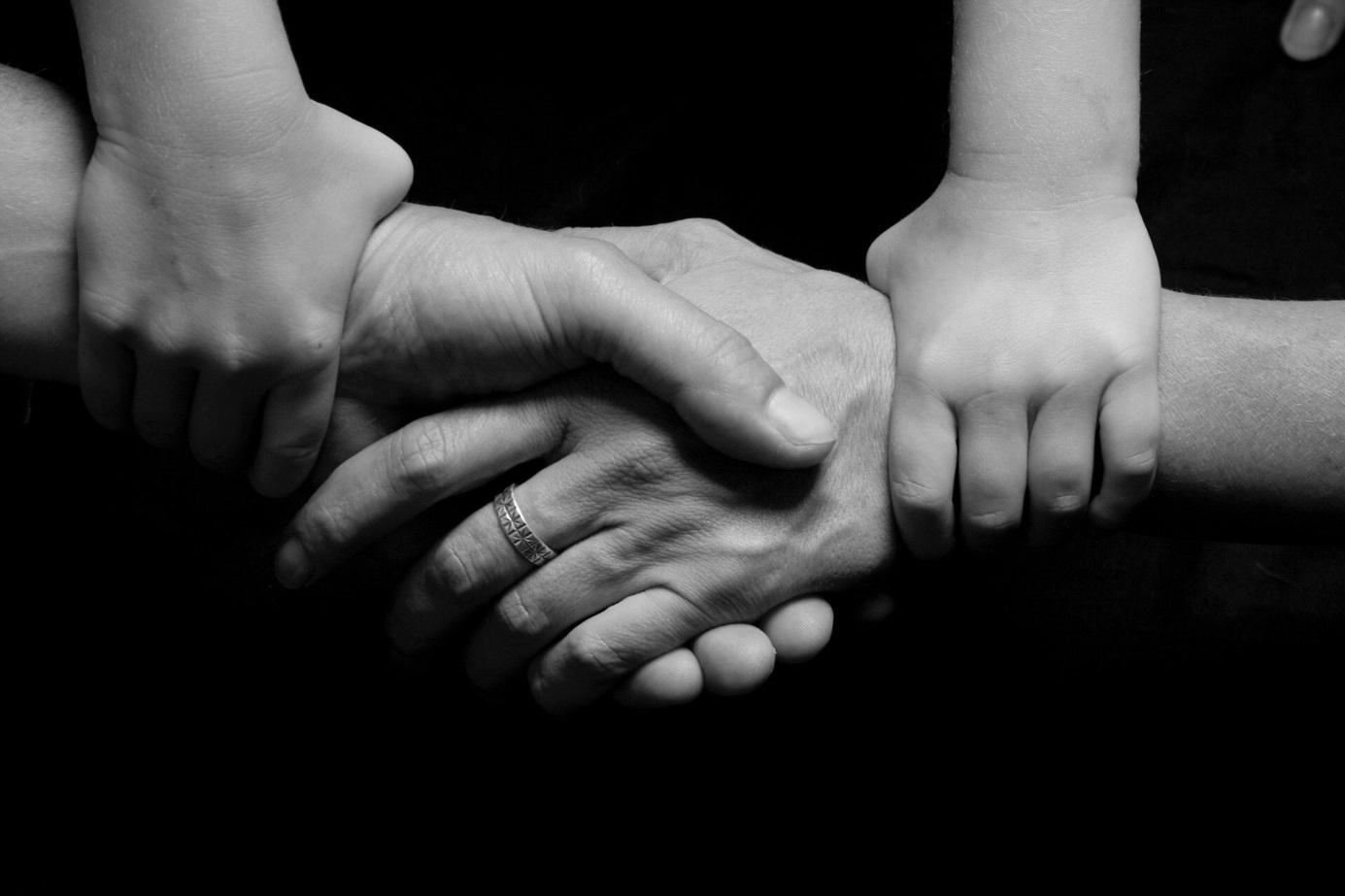 Kind hält die Hände seiner Eltern zusammen.