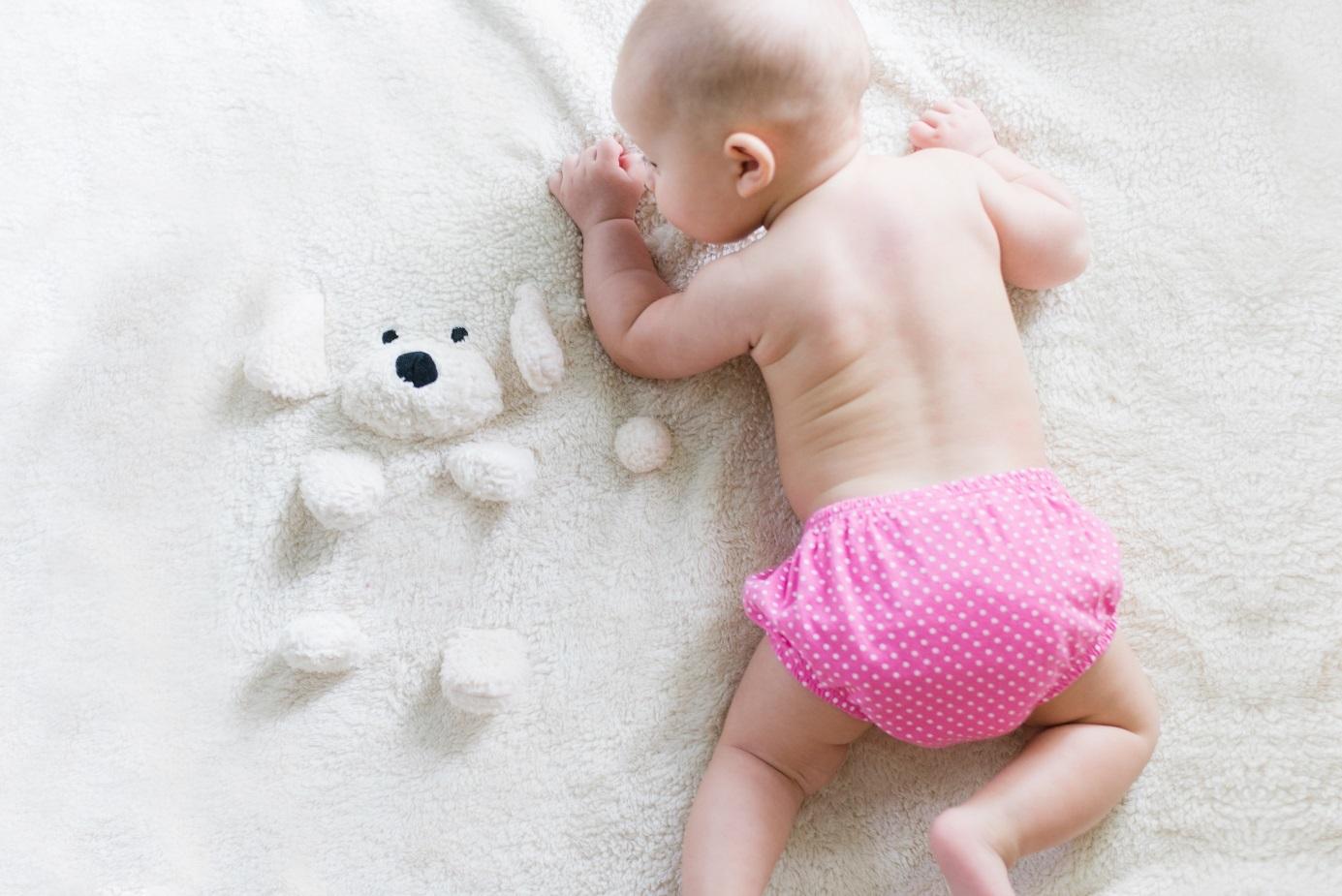 Ein Baby krabbelt auf einer Decke.