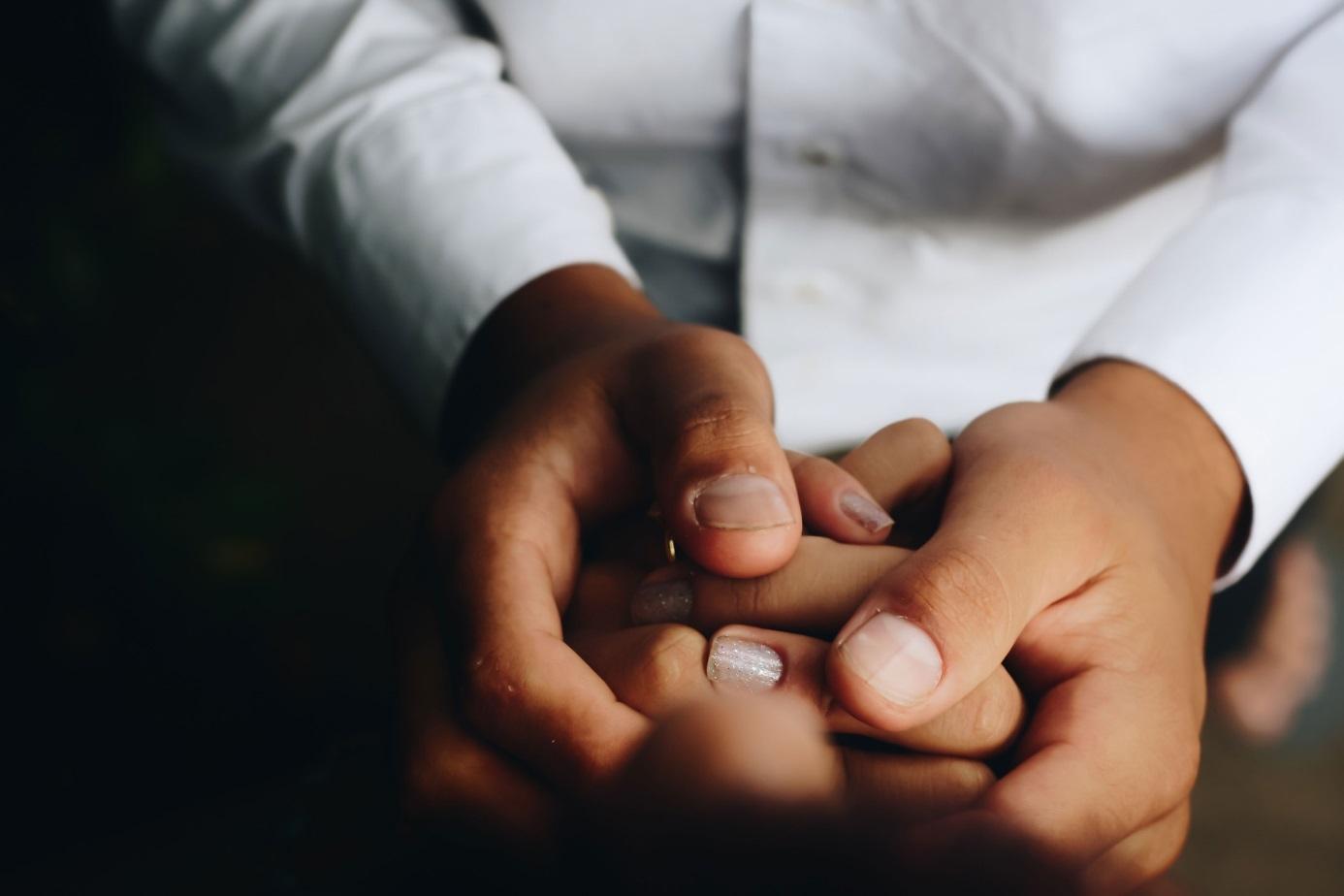 Männerhände umlegen eine andere Hand mit lackierten Fingernägeln.