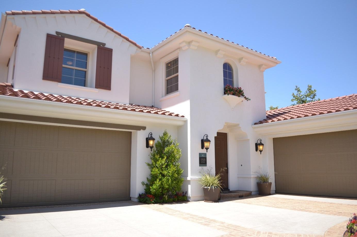 Ein Haus mit weißer Fassade und zwei Garagen.