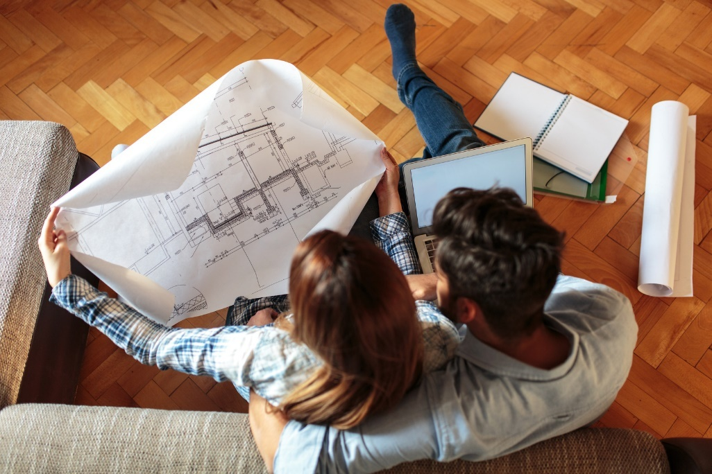 Paar sitzt zusammen und sieht sich Baupläne an.