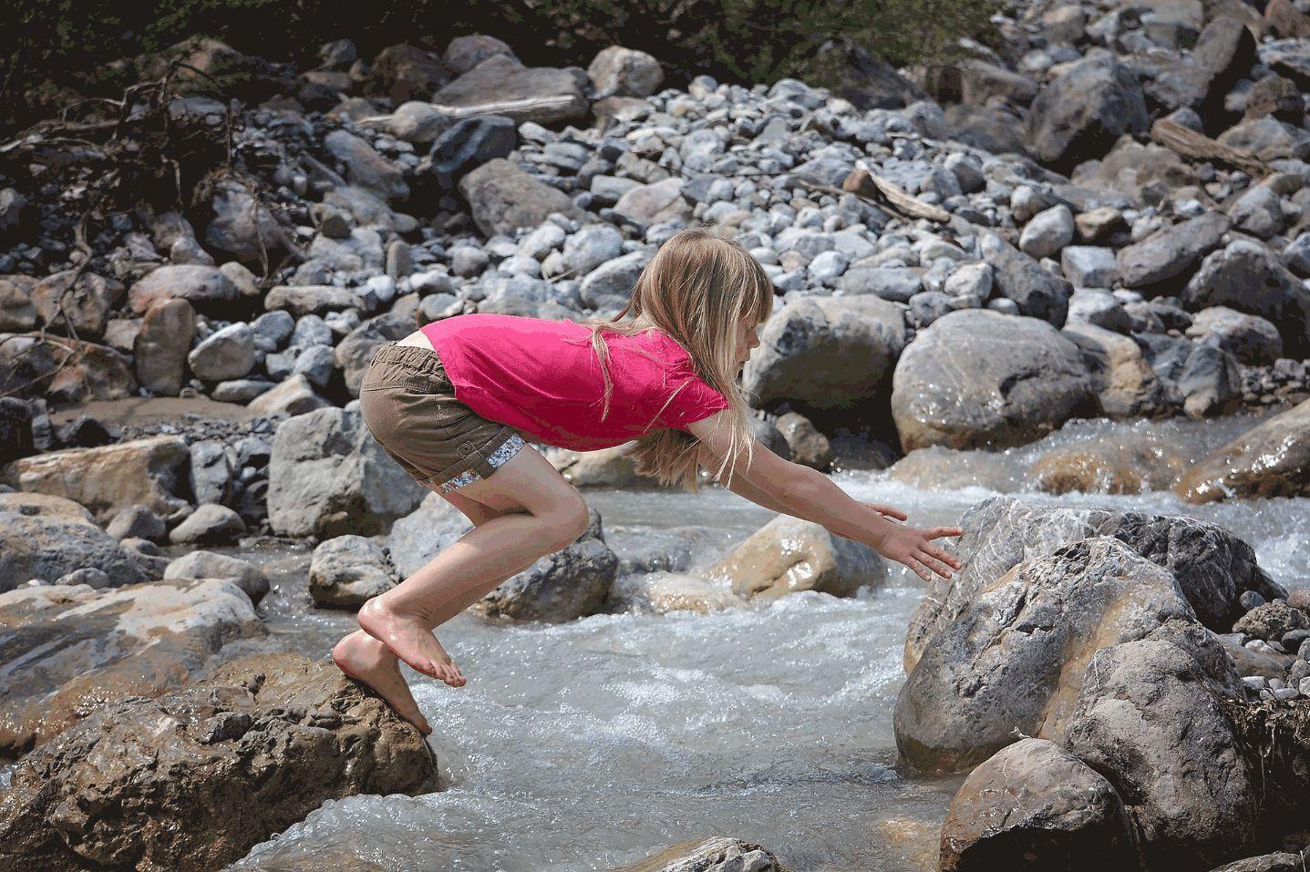 Mädchen klettert auf Steinen.